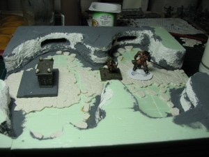 While a dwarven miniature only slightly protrudes over the walls, the Barbarian